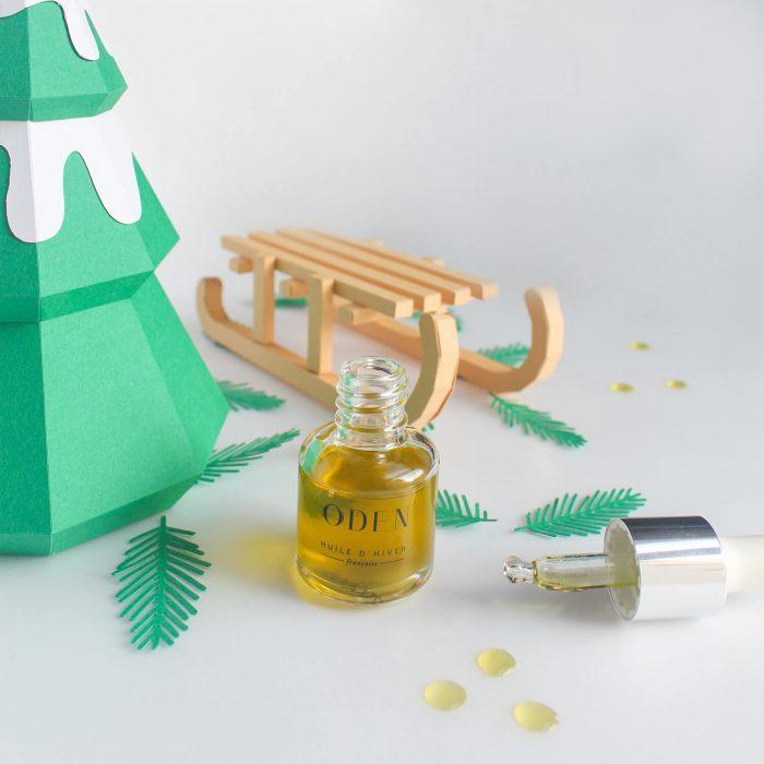 Huile d'hiver Oden flacon ouvert avec gouttes d'huiles. Paper art sapin et luge