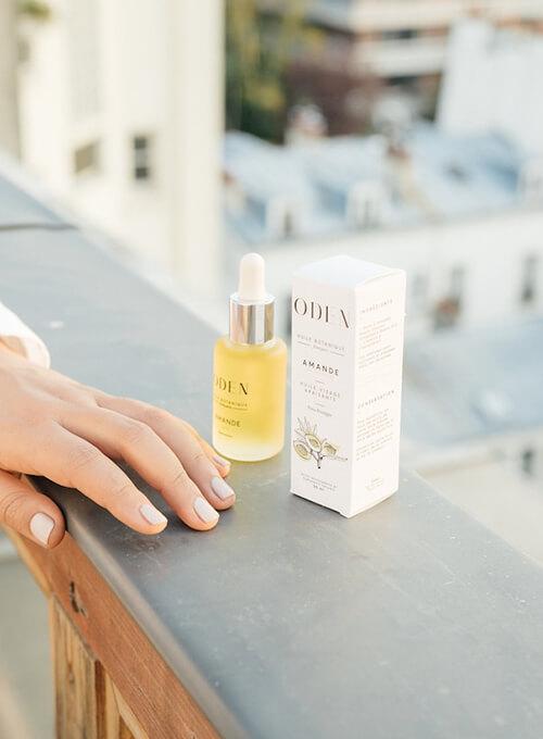 Huile botanique amande Oden au bord d'une terrasse vue sur les toits parisiens.