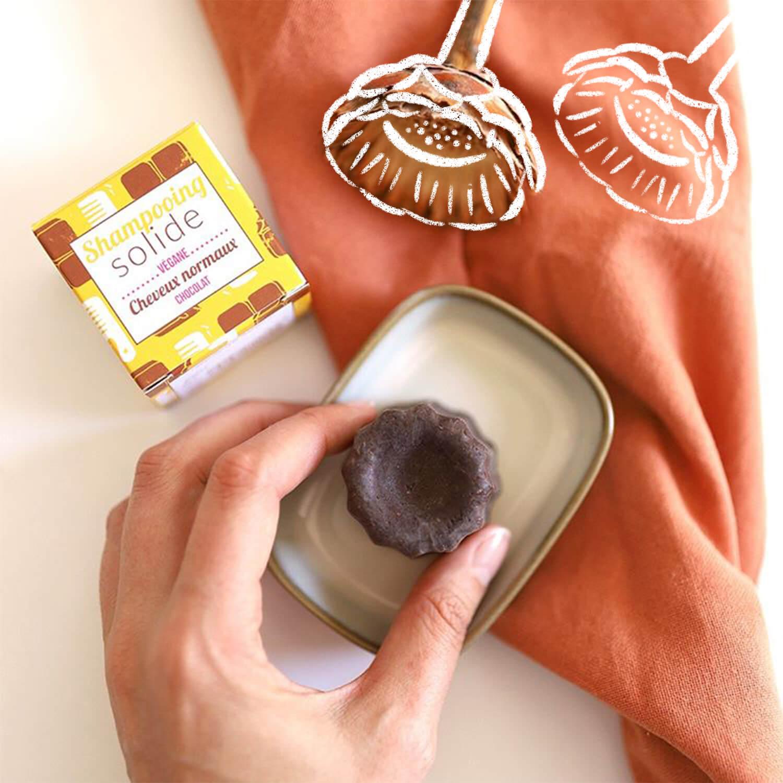 Shampoing solide chocolat Lamazuna dans une assiette tenue par une main.