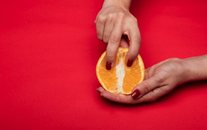 Orange entre les mains, ongles rouges. Fond rouge.