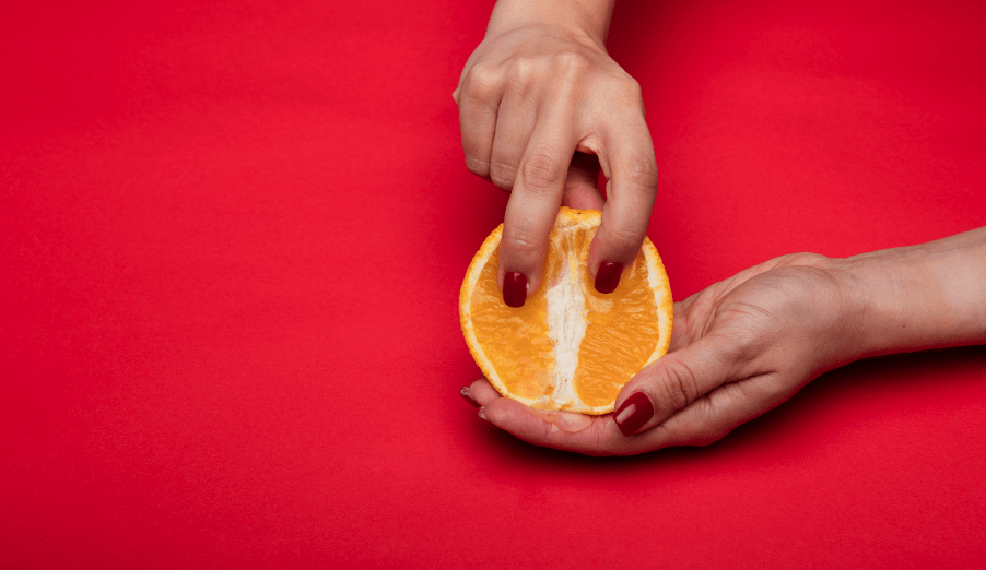Orange entre les mains, ongles rouges. Fond rouge.